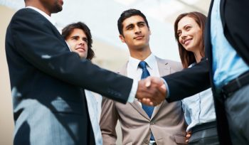 Portrait of hand shake between business associates with confident team